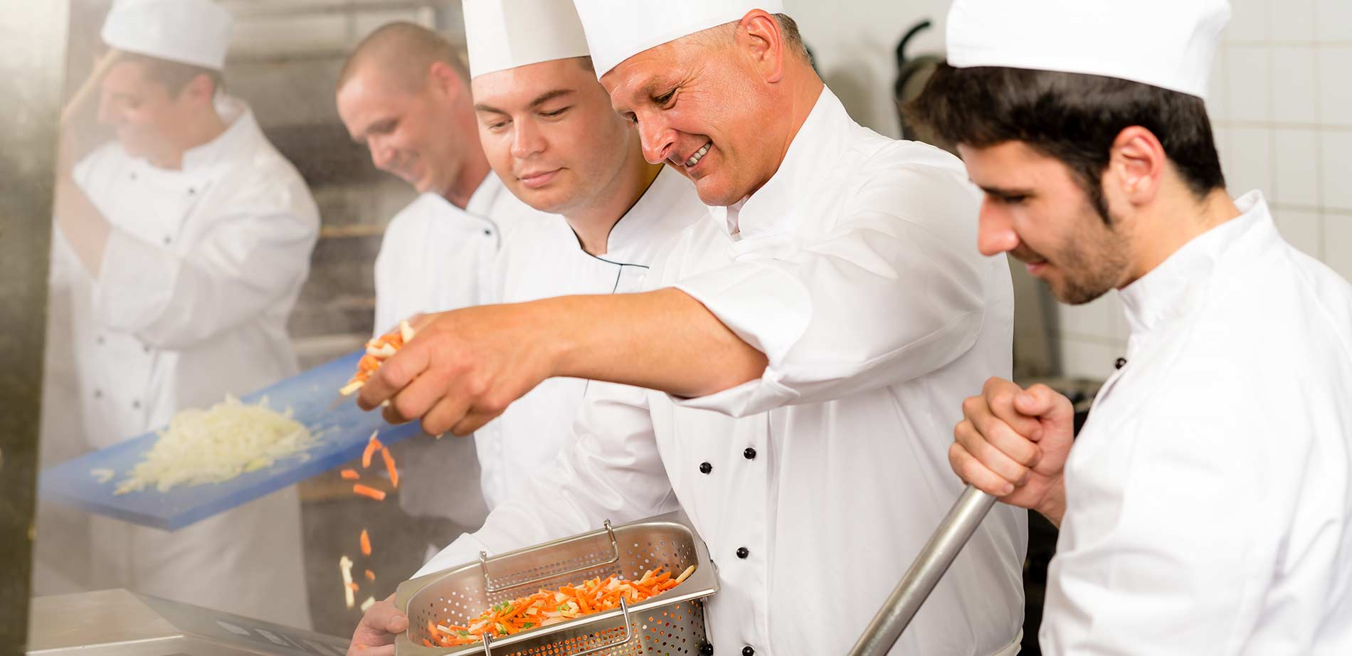 Chefs cooking in a commercial kitchen together.